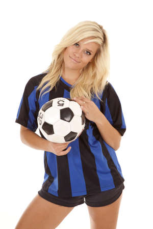 A woman holding on to her soccer ball in her soccer uniform with a smile on her face. photo