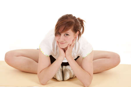 A woman sitting down and stretching out her legs with a smile on her face. Stock Photo - 12104867