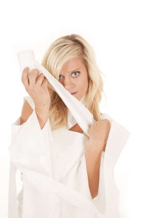 A woman all wrapped up in toilet paper with a confused expression on her face, holding the roll. photo