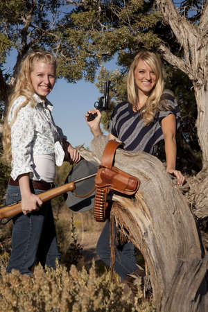 Two women with guns in the out doors with smiles on their faces. photo