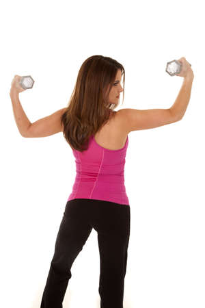A womans back to the camera lifting weights. photo