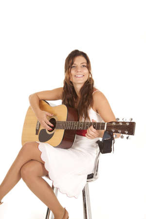 A woman in her white dress sitting on her stool playing her guitar with a smile on her face.
