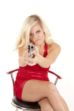 A woman with a angry expression on her face pointing a gun. photo