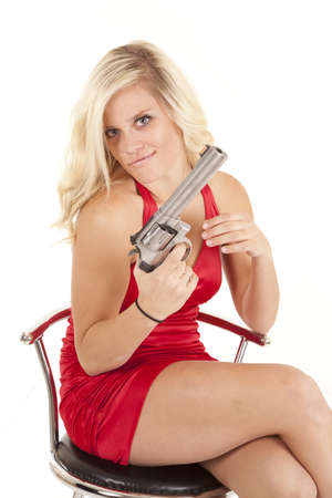 hand gun: A woman in her red dress holding on to a gun with  an evil expression on her face. Stock Photo