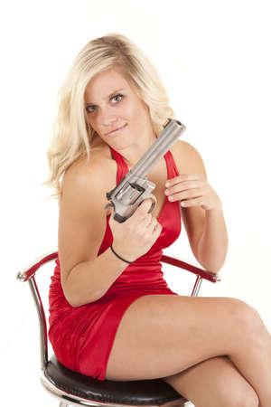 mujer con arma: Una mujer con su vestido rojo que sostiene a un arma de fuego con una expresión del mal en su cara.