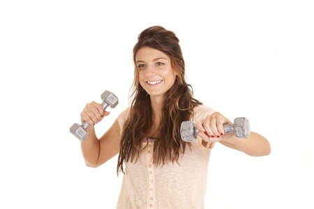 A woman with a smile on her face working out with weights. photo