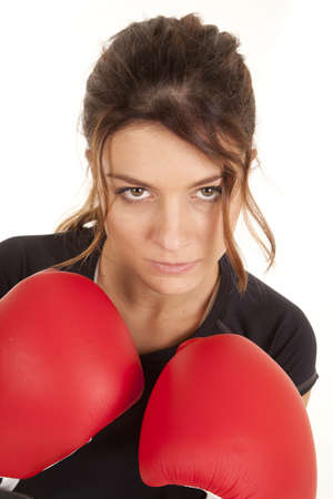 A woman with her boxing gloves up close to her face with a serious expression on her face. photo