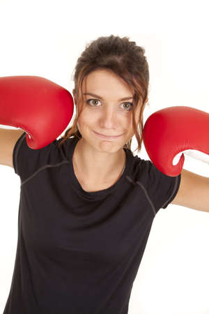 A woman with a funny expression on her face with her boxing gloves up by her face. photo
