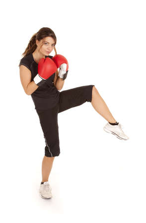 a woman standing and kicking her foot  with  her boxing gloves up close to her body. photo