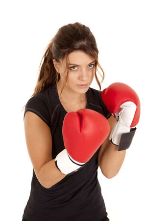A woman with her boxing gloves up close to her with a serious expression on her face. photo