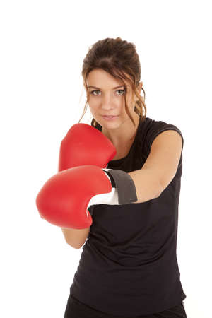 A woman with  a small smile on her face punching with her boxing gloves. photo
