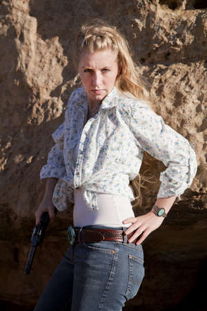 a woman standing in her western wear in the outdoors holding a gun. photo