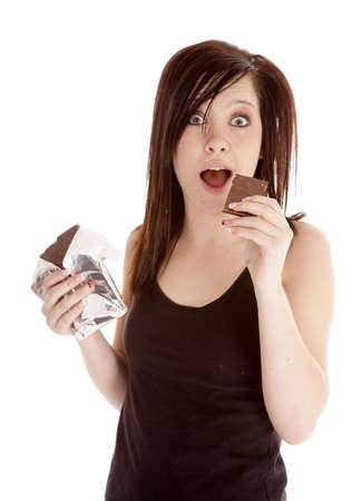 A woman getting ready to put some chocolate into her mouth with a happy expression on her face photo
