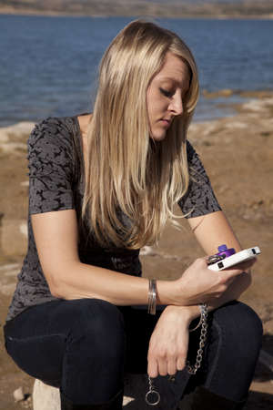 A woman sitting and feeling like she is chained to her cell phone. Stock Photo - 12104609