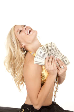 A woman being a genie holding a handful of cash with her head back laughing.