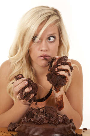 a woman chocolate cake all over her face and hands with a shocked expression on her face.
