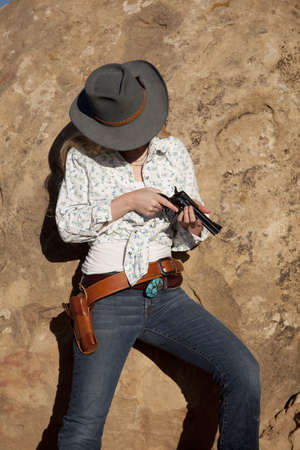 A woman checking her pistol looking down. photo