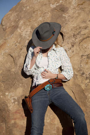 A woman leaning up against a rock in her cowgirl hat. photo