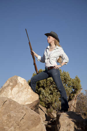 a woman standing up on top of rocks in her western wear holding a rifle. photo