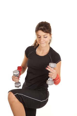 A woman concentrating and lifting weights with a serious expression on her face. photo