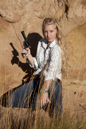 A woman kneeling down in the grass holding on to a gun with  a serious expression on her face.