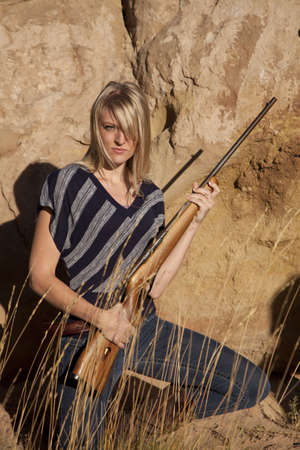 A woman kneeling down in the grass holding a rifle. photo
