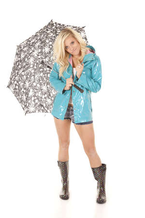A woman in her boots, rain coat, and umbrella with a smile on her face.