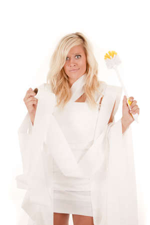 scrubber: A woman wrapped up in toilet paper holding a toilet scrubber with a funny expression on her face. Stock Photo