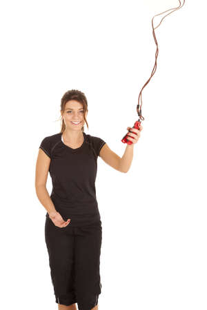 A woman standing and flinging her jump rope in the air with a smile on her face. photo