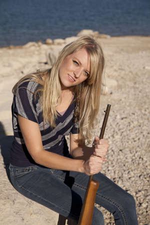 A woman sitting on a rock holding her rifle with  a small smile on her lips. photo