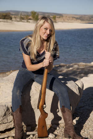 A woman sitting on the rock in her cowgirl boots  holding her rifle. photo