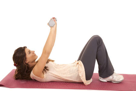 A woman laying on her back lifting weights and working out. photo
