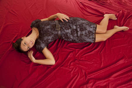 a woman laying on a red sheet in her fancy lace dress. photo