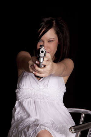 a woman on a black background holding a gun pointing it at the camera. photo