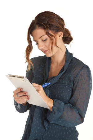 a woman taking notes and looking at what she is writing. photo
