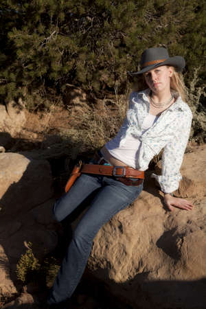A woman sitting on a rock wearing her cowgirl hat with her gun in her belt.