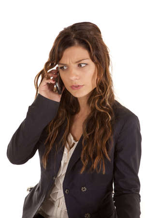 A woman listening to her cell phone with an upset expression on her face. photo