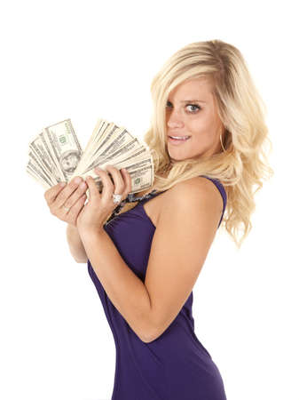 A woman wearing purple holding on to a fan full of money with a smile on her face.