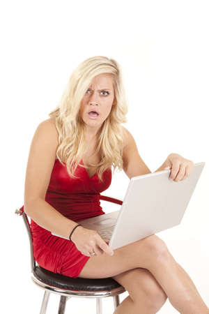 A woman with a shocked expression on her face upset at her laptop.