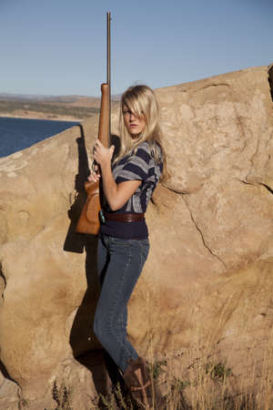A woman standing behind a rock with a serious expression on her face holding her gun. Imagens