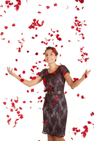 A woman with  a smiel on her face being showered with rose petals.