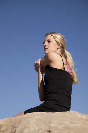 A woman sitting down on the rock stretching out her shoulder. photo