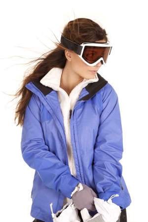 a woman in her ski clothes wearing her goggles with the wind blowing her hair.
