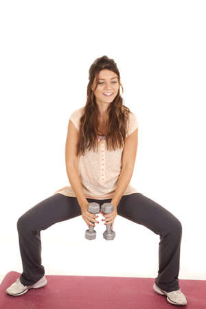 a woman working out doing squats holding weights with a smile on her face. photo