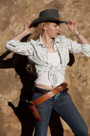 A woman in her cowgirl out fit holding on to her hat with her gun in her holster.