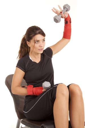 brunett: A woman sitting on a bench lifting weights.