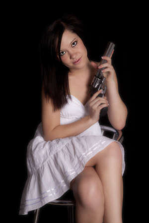 a woman in a white dress holding a gun with a serious expression on her face. photo