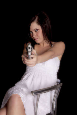 A woman in a white dress pointing a gun at the camera. Stock Photo