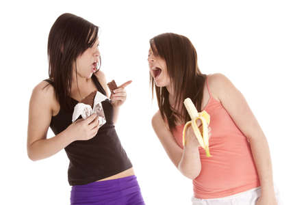 A woman wanting to eat her friends chocolate bar rather then her fruit. photo