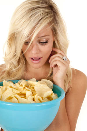 a woman holding on to a huge bowl full of chips wondering if she got too many.   photo